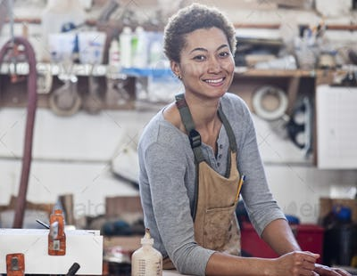 View of a smiling black woman factory worker at her work station in a woodworking factory.