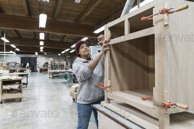 A Black woman carpenter working on a cabinet project in a large woodworking shop.