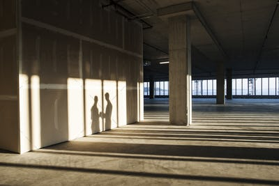 Shadows of business people cast on the sheet rock wall of a large empty raw office space.