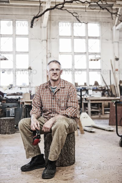 Caucasian man factory worker sitting on a stool in a woodworking factory.