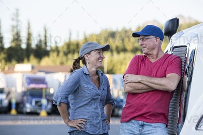 Caucasian man and woman driving team talking in front of a large truck at a truck stop.