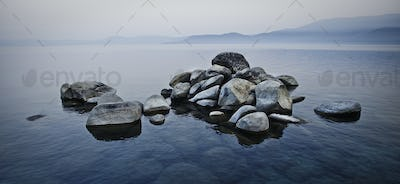 A pile of stones rising above the water level in a lake in a misty landscape.