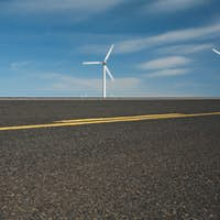 Three wind turbines on the horizon and a road runing through the plains near the Columbia River