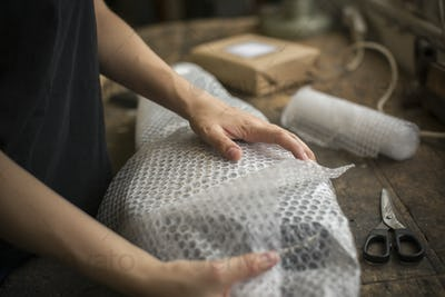 A woman wrapping an item in bubble wrap, a parcel being prepared for despatch.