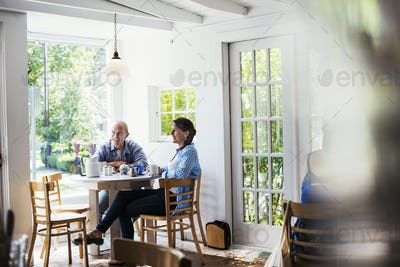 Two people seated at a coffee shop table by a window.  Blurred foreground.