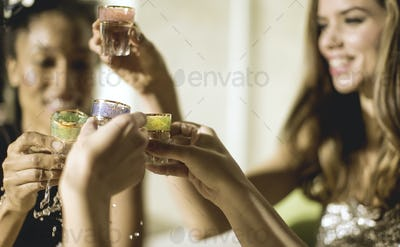 Two young women at a party in sequined dresses drinking and laughing