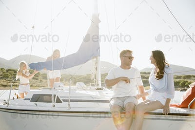 Man and woman sitting on a sail boat.