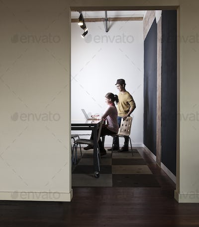 Hispanic male and caucasian female working on a laptop computer in a small conference room.