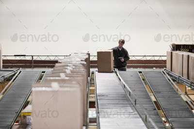 Causcasian warehouse worker in a large distribution warehouse, showing products stored in cardboard