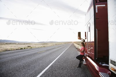 Female truck driver standing next to the cab of her truck near the highway in eastern Washington,