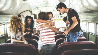 A group of young people in a party on a school bus.