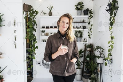 Female owner of plant shop smiling at camera, a selection of plants on wooden shelves.