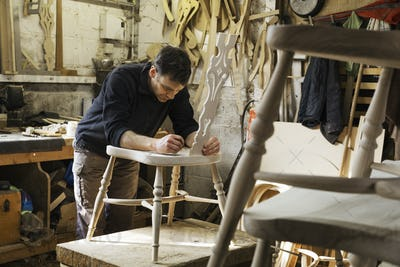 Man standing in a carpentry workshop, working on a wooden chair.