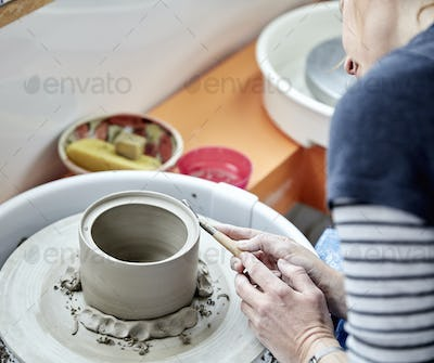A person using a pottery wheel finishing and shaving curls of clay off the side of a round clay pot.