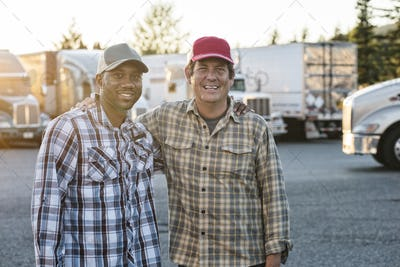A caucasian man and a black man truck driving team together in a truck stop parking lot.