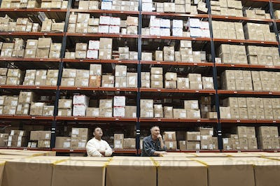 Two male warehouse workers checking inventory in a large distrubiton warehouse full of products