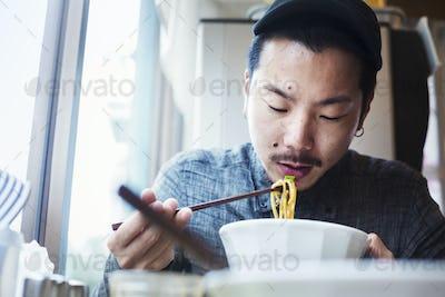 A ramen noodle cafe in a city.  A man sitting eating ramen noodle soup dish.