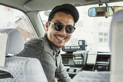 A man wearing sunglasses and baseball hat in the passenger seat of a car turning around and smiling.