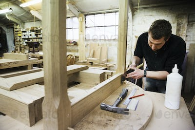 Man standing in a carpentry workshop, working on the skirting of a wooden table with a hand tool.