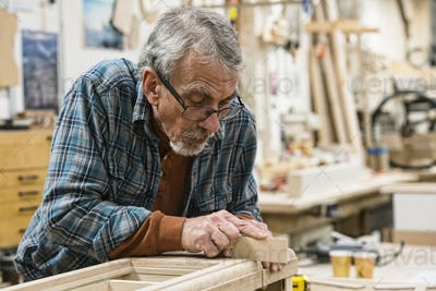 Senior Caucasian  carepenter sanding a wooden cabinet part in a large woodworking shop.
