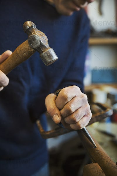 Man standing in a workshop, holding a hammer and wood chisel, working on a piece of wood.