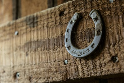 A metal horseshoe nailed onto a wooden beam.