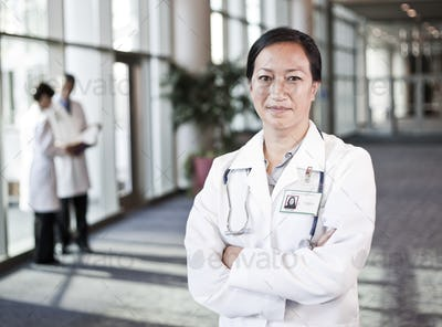 Asian woman doctor in lab coat with stethescope.