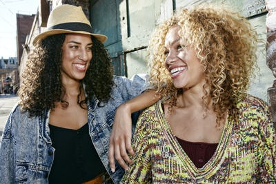 Portrait of two smiling young women with long curly black and blond hair, looking at each other.