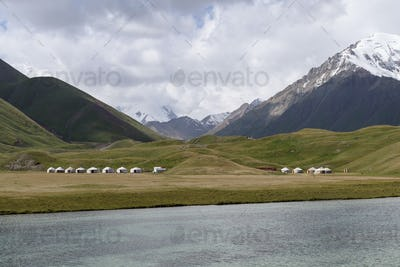 Landscape view with lake and snow capped mountains, Tulpar Kul, Kyrgyzstan.