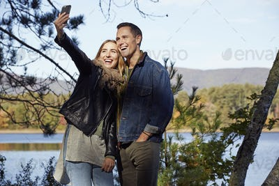 Two people, man and woman taking a selfie on the shore of a lake in autumn.