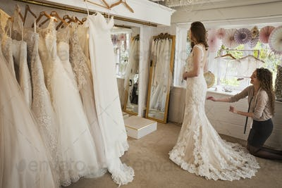 Rows of wedding dresses on display. A young woman in a full length white wedding dress, looking at