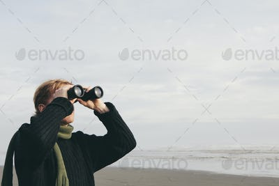 Middle aged man standing on a beach, looking through binoculars at Seabrook, Washington, USA.
