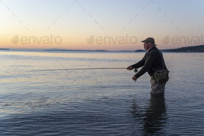 A side view of a fly fisherman at sunrise casting for salmon and searun coastal cutthroat trout from