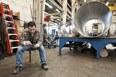 HIspanic man factory worker checking a part inventory on his cell phone in a sheet metal factory.