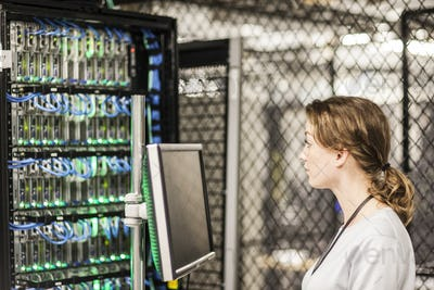 Caucasian woman technician doing diagnostic tests  on computer servers in a server farm.