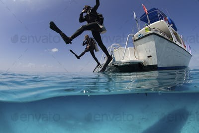 Over/under view showing divers performing giant stride entry into the clear calm waters of the