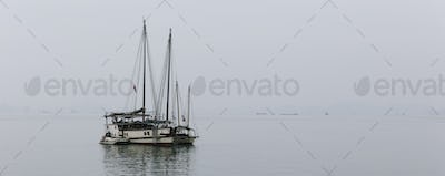 A boat sailing in open water in foggy conditions.
