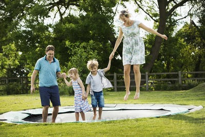Man, woman, boy and girl holding hands, jumping on a trampoline set in the lawn in a garden.