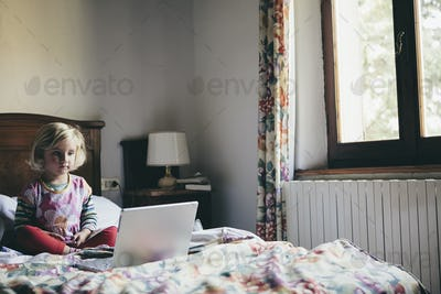 A three year old girl sitting on a bed in a hotel room, looking at a laptop computer screen