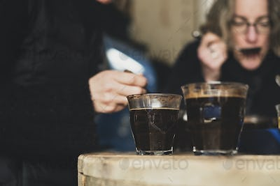 Close up of two glasses with coffee standing on wooden table, people in background.