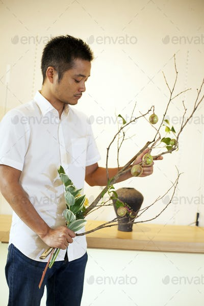 Japanese man standing in flower gallery, working on Ikebana arrangement.