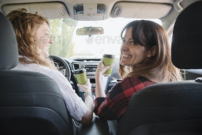 Two women in a car on a road trip. View from behind.