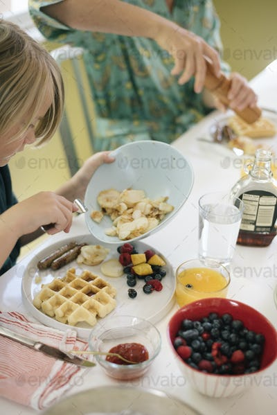 Boy sitting at breakfast table, waffles, fruit and juice.