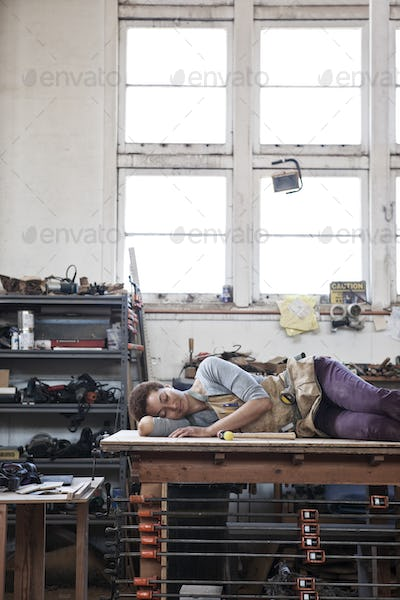 Black woman factory worker taking a nap on top of a work station in a woodworking factory.