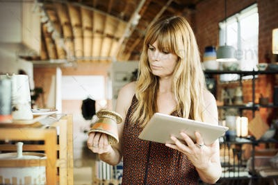Woman in a shop, holding a digital tablet and small ceramic pot.
