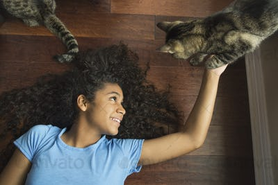 A girl lying on her back stroking a cat.
