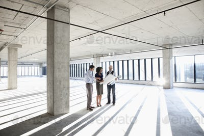 Group of business people looking at a new empty raw office space.