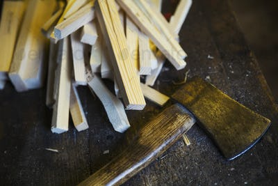 Close up of wooden pegs and a hand axe in a sailmaker's workshop.