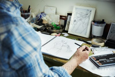 An artist working, holding a pencil over a sketch in progress in an open sketchbook.