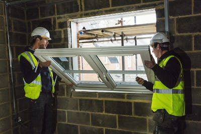 Two builders in hard hats and high visibility jacket fitting a window frame.